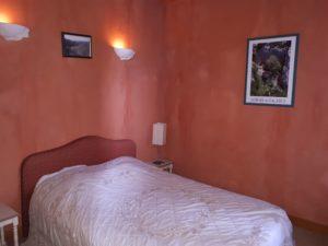 Une belle chambre avec un lit double sous une imposante charpente avec son petit balcon ouvragé.