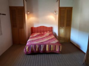 Le Tineiral à Néffies, apartment Les Romarins. The large bedroom includes a double bed and has views onto the garden and surrounding vineyards.