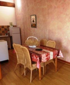 Un coin repas et salon avec canapé lit et télévision.