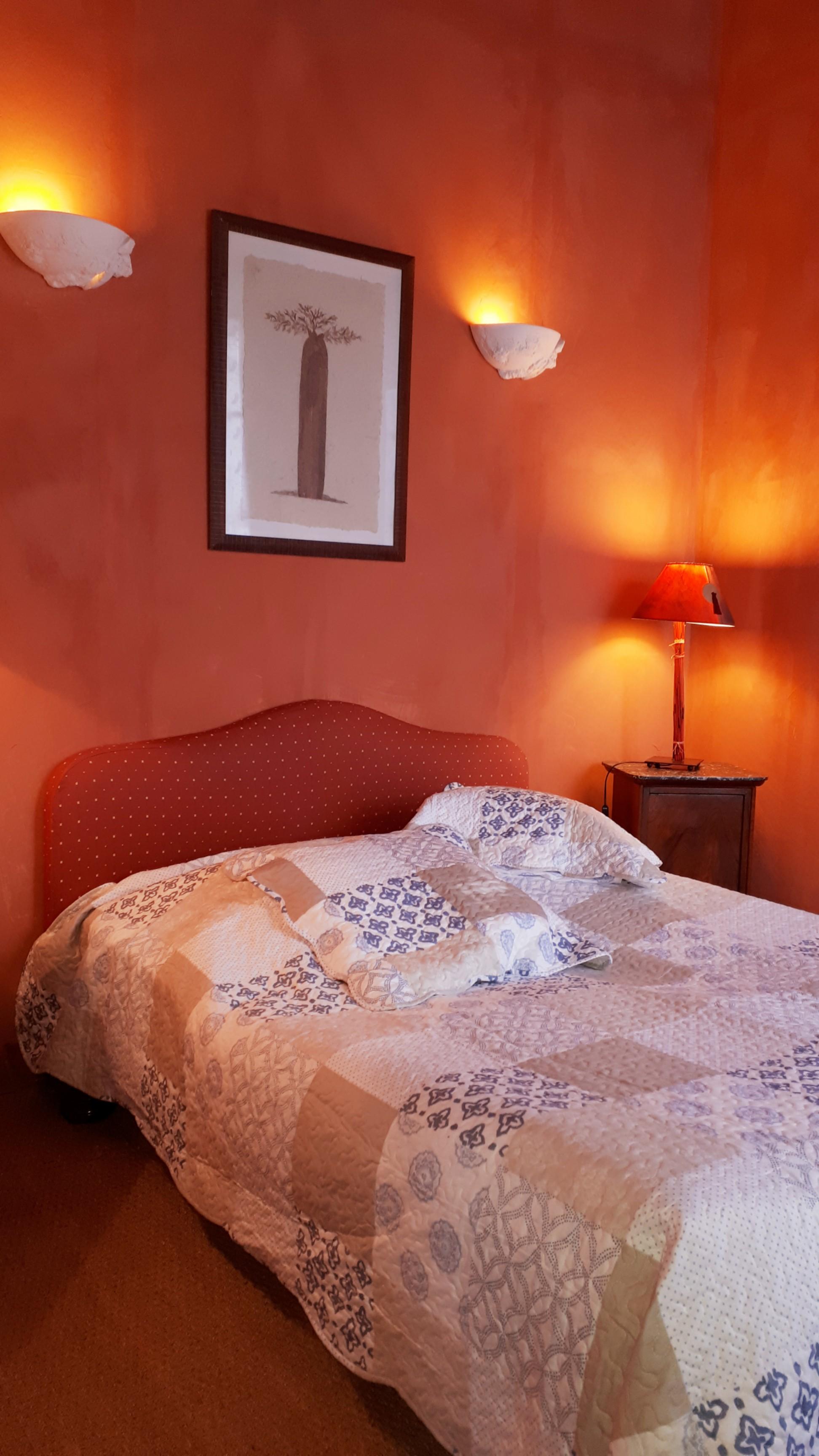 Le gite Les Lavandes proche de Pézenas sud de france. Une belle chambre avec un lit double sous une imposante charpente avec son petit balcon ouvragé.