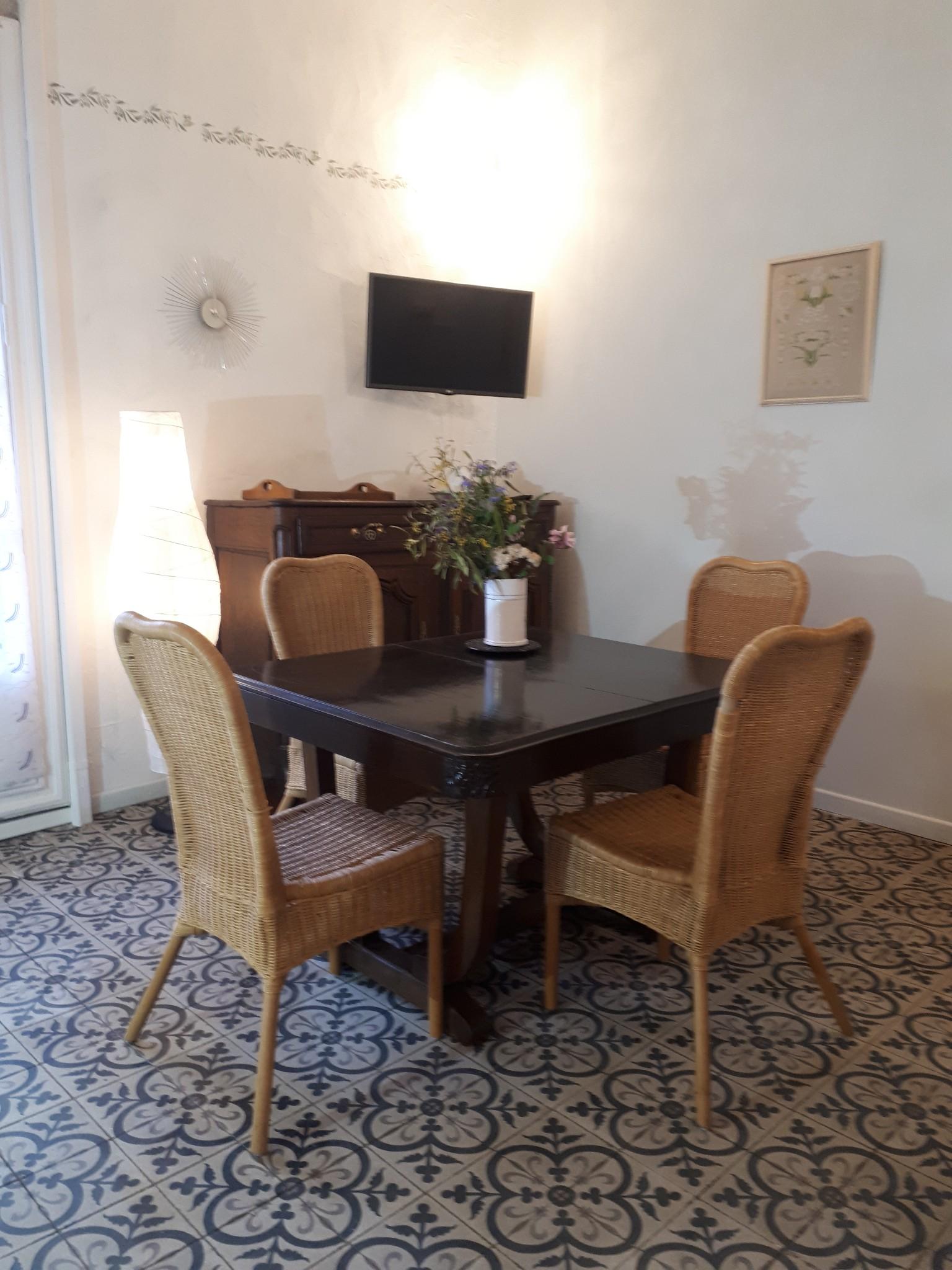 Le Tineiral à Néffiès Gite les Bruyeres : Un coin repas un coin salon avec canapé-lit double et télévisionet ses vastes volumes sous l'imposante charpente.